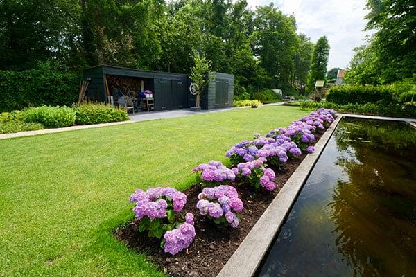 Tuin met beplanting, gazon en vijver