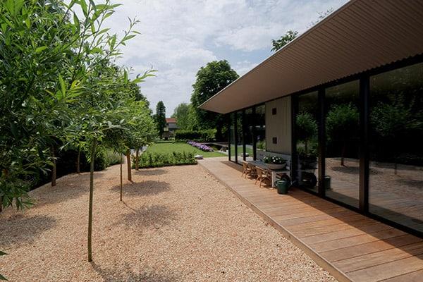 Aangelegde tuin met grind, fruitbomen en hardhouten vlonder