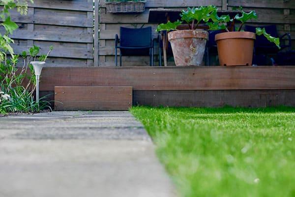 Tuinrenovatie met hardhouten vlonder, gazon en bestrating